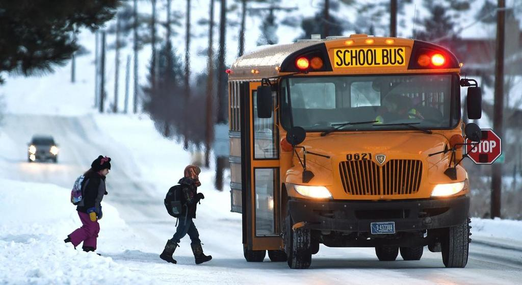 Student stepping on school bus on snowy day